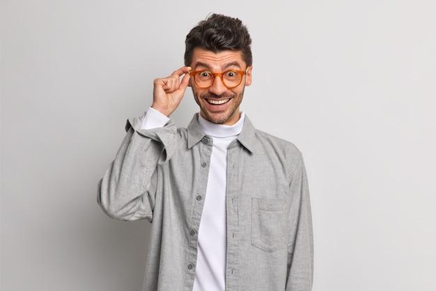 Vrolijke knappe europese man ziet er gelukkig uit door een bril gekleed in grijs shirt glimlacht zorgeloze poses binnen. gelukkige mannelijke werknemer klaar voor de volgende taak. positieve emoties concept