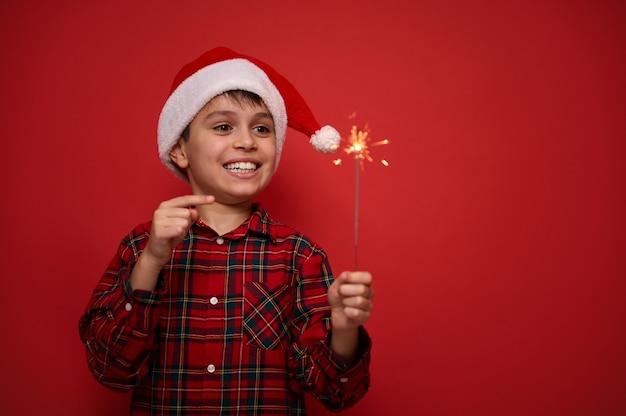 Vrolijke knappe geweldige preteen jongen in kerstmuts en geruite rode shirt verheugt zich op het kijken naar bengaalse kerstverlichting, sterretjes in zijn handen, staat tegen een gekleurde achtergrond met kopie ruimte voor advertentie