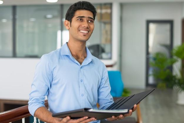 Vrolijke knappe indiase zakenman met documenten