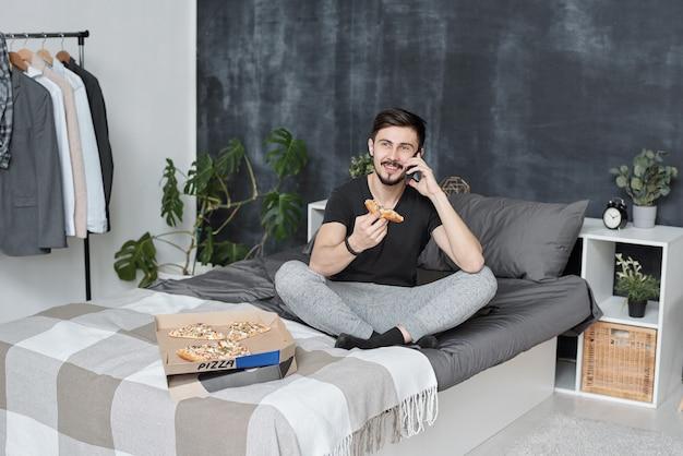 Vrolijke knappe jonge bebaarde man zittend op bed en chatten via de telefoon tijdens het eten van pizza thuis