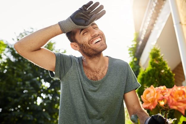 Vrolijke knappe jonge blanke man in blauw t-shirt en handschoenen lachend met tanden, moe van hard werken in de tuin. boer planten bladeren in plattelandshuis
