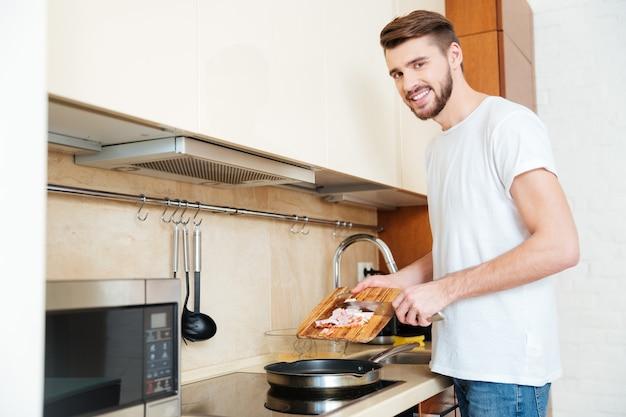 Vrolijke knappe jonge man frituren ontmoeten met behulp van pan en glimlachen