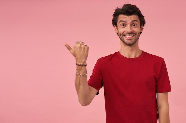 Vrolijke knappe jonge man met stoppels in rode t-shirt glimlachend en wijst naar de zijkant