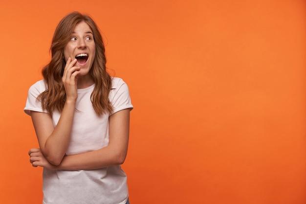 Vrolijke knappe jonge vrouw met rood krullend haar poseren, haar gezicht aanraken met de hand en de mond wijd openen