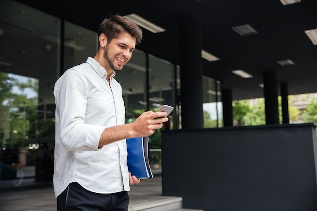 Vrolijke knappe jonge zakenman die smartphone in de stad gebruikt