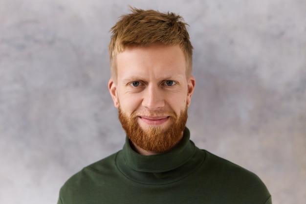 Vrolijke knappe jongeman met stijlvol kapsel, nette bijgesneden baard en blauwe ogen die positieve emoties uitdrukken. mensen, mannelijkheid, herenkleding, stijl, mode en verzorgingsconcept