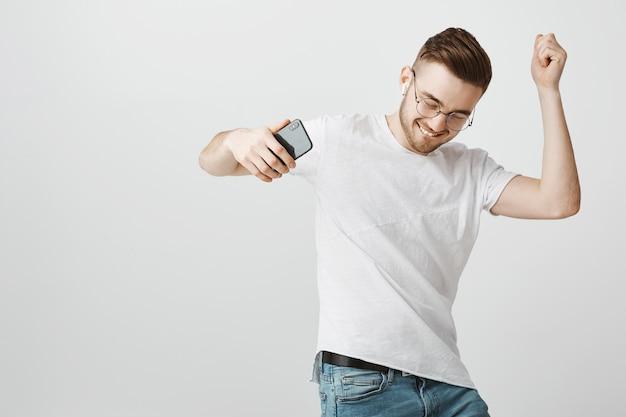 Vrolijke knappe jongen in glazen dansen op muziek in draadloze koptelefoon met mobiele telefoon in de hand