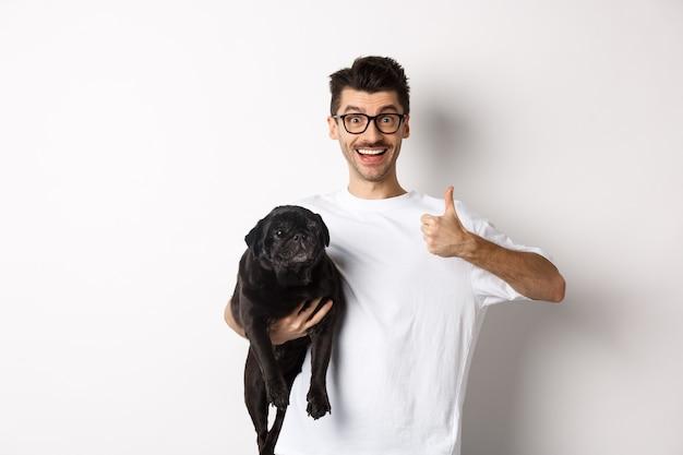 Vrolijke knappe man die hond vasthoudt en een goed teken toont, product goedkeurt of aanbeveelt. hipster-man draagt een schattige zwarte mopshond en ziet er tevreden, witte achtergrond uit.
