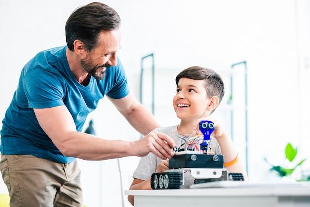 Vrolijke knappe man die zijn zoon helpt terwijl hij thuis een nieuw robotapparaat test