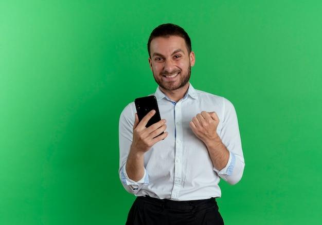 Vrolijke knappe man houdt telefoon houdt vuist op zoek geïsoleerd op groene muur