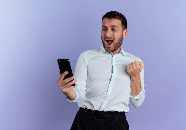 Vrolijke knappe man houdt vuist vasthouden en kijken naar telefoon geïsoleerd op paarse muur