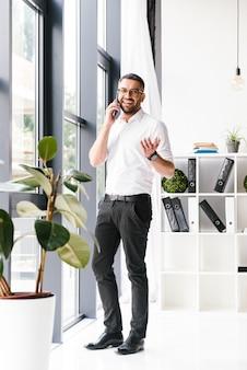 Vrolijke knappe man in formele kleding met een aangenaam mobiel gesprek, terwijl hij in de buurt van een groot raam op kantoor staat