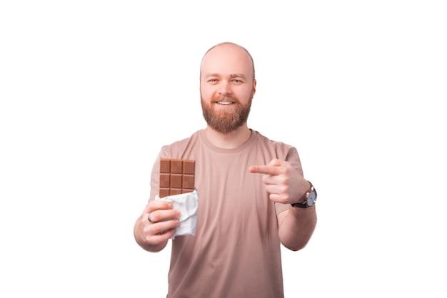 Vrolijke knappe man met baard wijzend op blok chocolade staande op wit