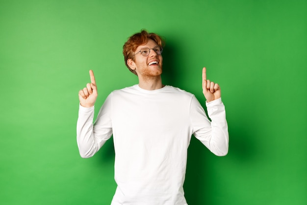 Vrolijke knappe man met een bril die de verkoopdeal bekijkt, wijst en omhoog kijkt met een gelukkige en dromerige glimlach, staande over een groene achtergrond.