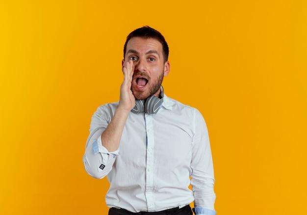 Vrolijke knappe man met een koptelefoon op de nek houdt de hand dicht bij de mond en doet alsof hij iemand belt die op een oranje muur is geïsoleerd