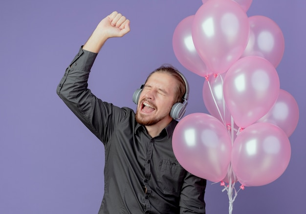 Vrolijke knappe man op koptelefoon houdt helium ballonnen vast en steekt vuist omhoog geïsoleerd op paarse muur