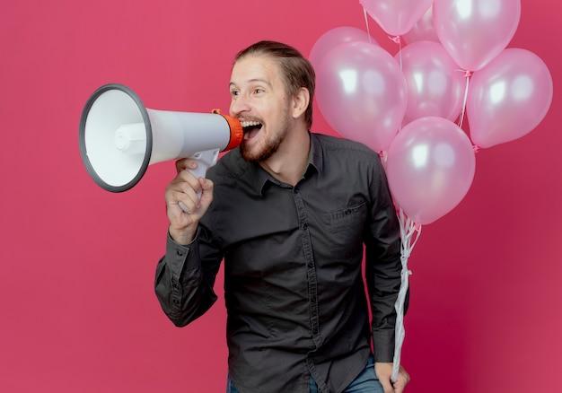 Vrolijke knappe man staat met helium ballonnen met luide spreker kijken naar kant geïsoleerd op roze muur