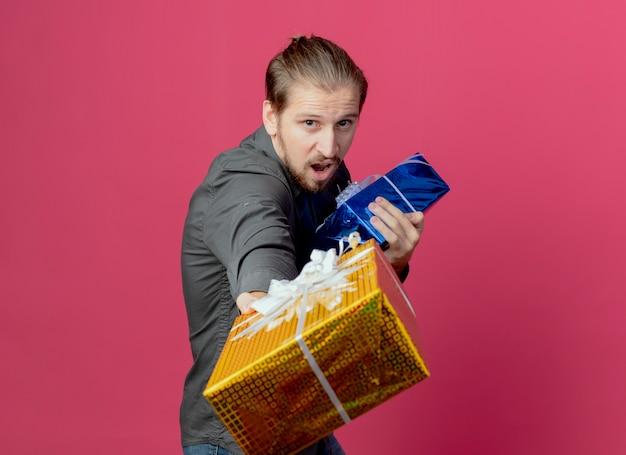 Vrolijke knappe man staat zijwaarts met geschenkdozen op zoek geïsoleerd op roze muur