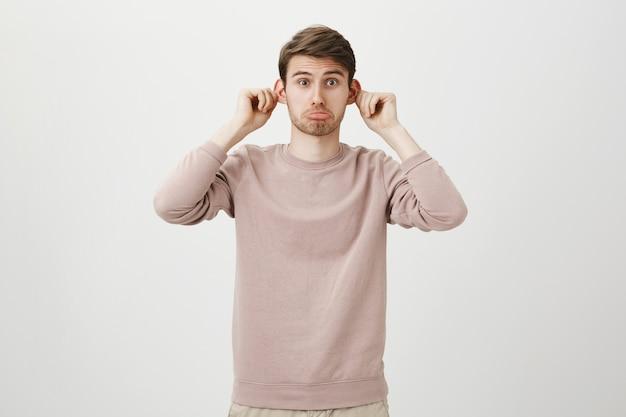 Vrolijke knappe man trekt oren en grimassen