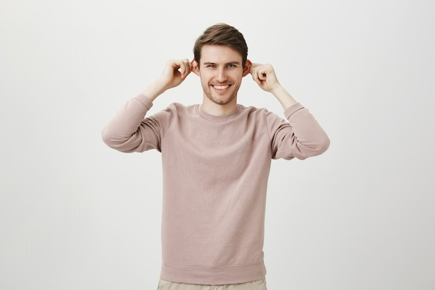 Vrolijke knappe man trekt oren en lacht