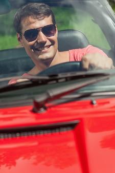 Vrolijke knappe man zijn cabriolet rijden