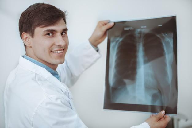Vrolijke knappe mannelijke arts die aan de camera glimlacht, longenröntgenstraal van een patiënt onderzoekt
