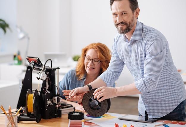 Vrolijke knappe positieve ontwerper die naar je kijkt en glimlacht terwijl hij het filament naar de 3d-printer leidt