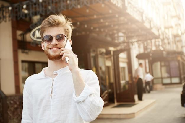 Vrolijke knappe roodharige man met trendy kapsel en baard, in gloednieuwe zonnebril praat met zijn vrouw aan de telefoon en voelt zich gelukkig.