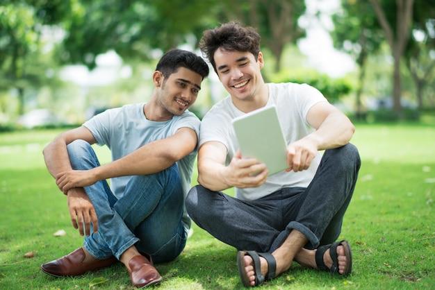 Vrolijke knappe studentenjongens die op video op tablet letten