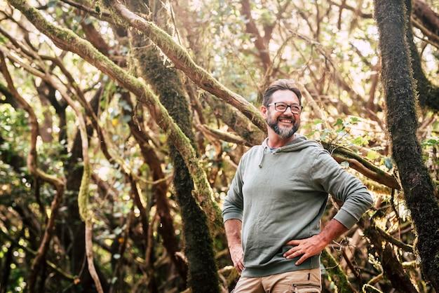 Vrolijke knappe volwassen man in het bos