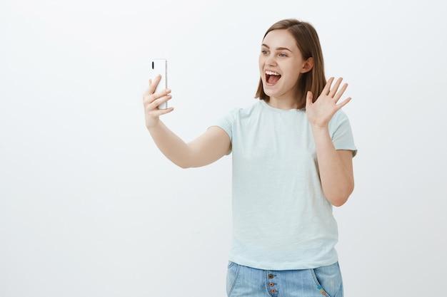 Vrolijke, knappe vrouw die via smartphone spreekt videoboodschap met handpalm zwaait, breed glimlachend naar het scherm van het apparaat hallo zegt communiceren via internet