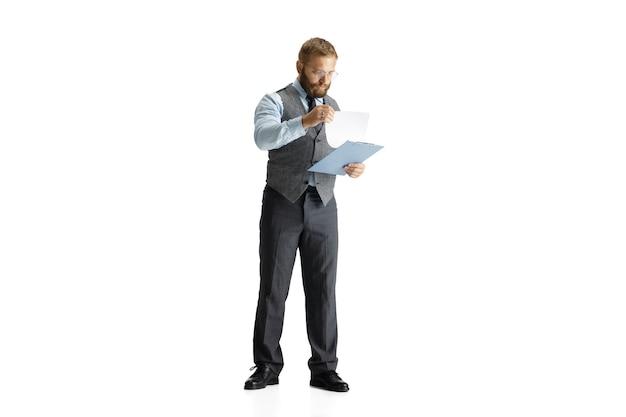 Vrolijke knappe zakenman die over witte studiomuur wordt geïsoleerd