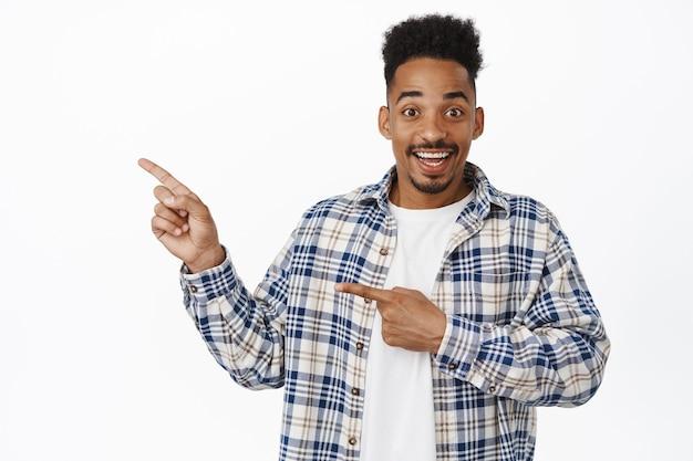 Vrolijke knappe zwarte man, jonge kerel met snor en stijlvol kapsel, wijzende vingers naar links bij verkoop, logo banner tonen, gelukkig lachend op wit