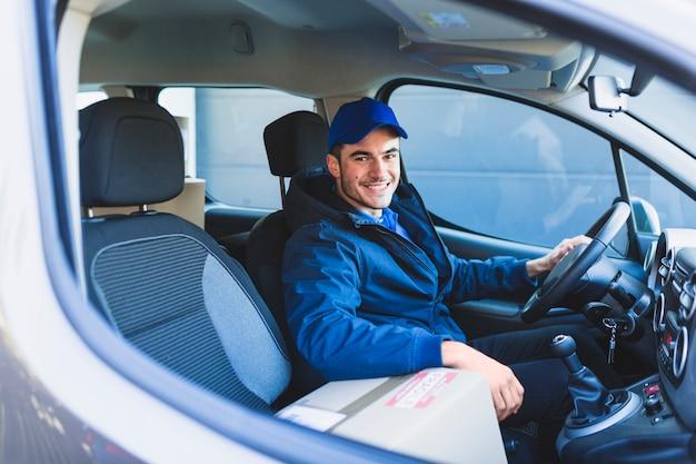 Vrolijke koerier in auto die bij camera glimlacht