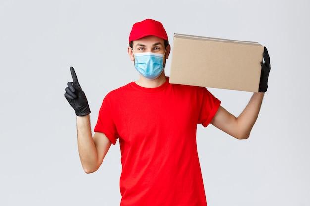 Vrolijke koerier in gezichtsmasker, handschoenen en uniform, draag uw pakket naar de deur, naar boven wijzend, houd de doos bij de bestelling