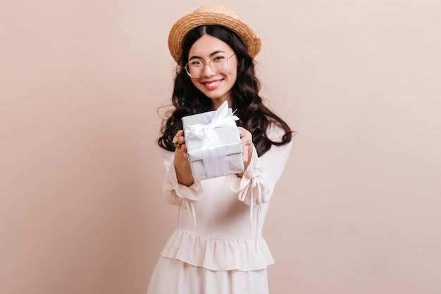 Vrolijke koreaanse vrouw die geschenk toont. lachend aziatisch model dat in hoed huidige doos houdt.