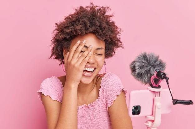 Vrolijke, krullende afro-amerikaanse vrouw die influencer lacht, houdt gelukkig de hand op het gezicht en heeft een grappig gesprek met abonnees poses tegen roze achtergrondgeluid