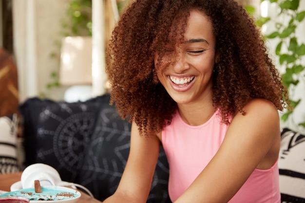 Vrolijke krullende afro-amerikaanse vrouw lacht luid als ze een grappig verhaal van een vriend hoort, vrije tijd doorbrengt in positief grappig gezelschap, grappen vertelt of anekdotes aan elkaar vertelt. geluk en een hoge geest.