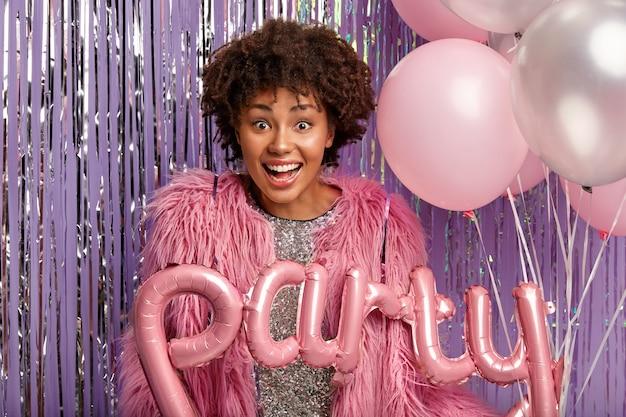 Vrolijke krullende donkere vrouw in roze jas, draagt ballonnen