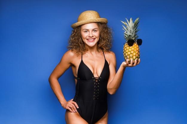 Vrolijke krullende haarvrouw die verse ananas met blauwe zonnebril houdt.