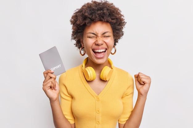 Vrolijke krullende vrouw balt vuist verheugt zich toekomstige reis naar het buitenland tijdens vakantie houdt paspoort draagt koptelefoon om nek gekleed in gele kleding geïsoleerd over witte muur