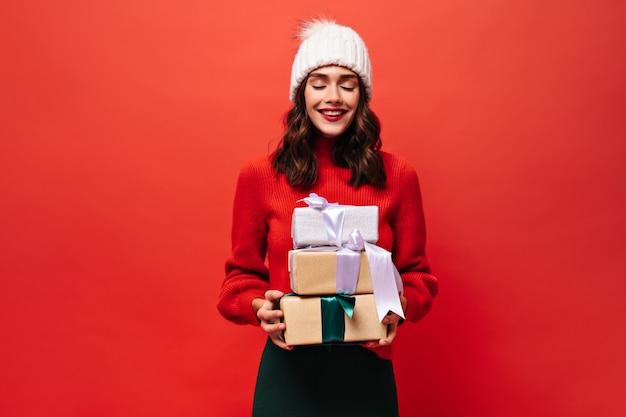 Vrolijke krullende vrouw in felrode trui, gebreide muts vormt gesloten ogen en houdt geschenkdozen op geïsoleerde rode muur