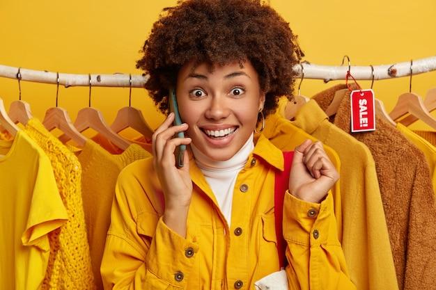 Vrolijke krullende vrouw met dolgelukkig gezicht, brede glimlach, gebalde vuisten opheft, belt iemand via smartphone, draagt boodschappentas op schouder, koopt kleding.