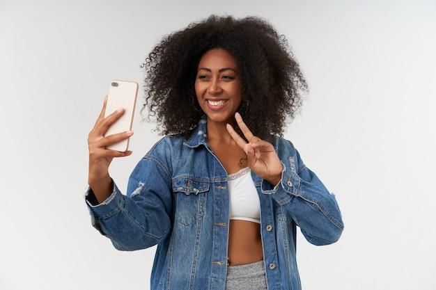 Vrolijke krullende vrouw met donkere huid die hand opsteekt met mobiele telefoon en gelukkig naar de camera kijkt, overwinningsteken toont met haar vingers terwijl ze selfie maakt, poserend over witte muur