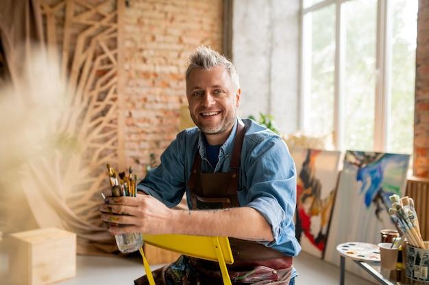 Vrolijke kunstenaar in werkkleding zittend op een stoel