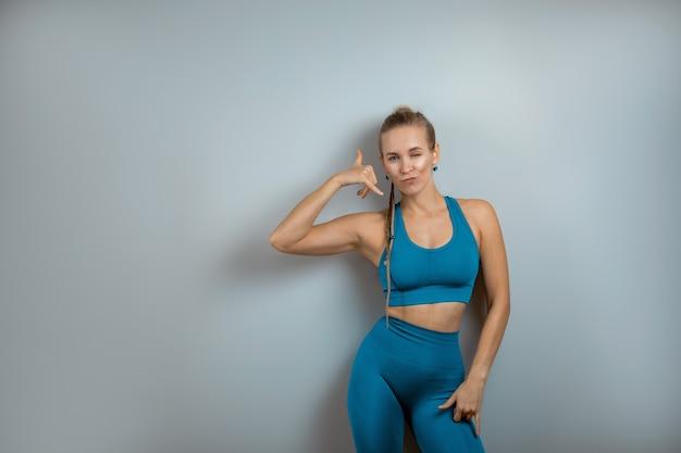 Vrolijke, lachende gymnastiek meisje toont met haar handen op een tekstplaats, kopie ruimte, mooi lichaam op een grijze vloer wandoppervlak in een yogastudio klasse