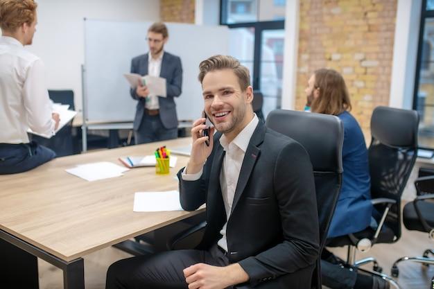 Vrolijke lachende jonge man in pak praten over smartphone aan tafel en collega's achter in kantoor