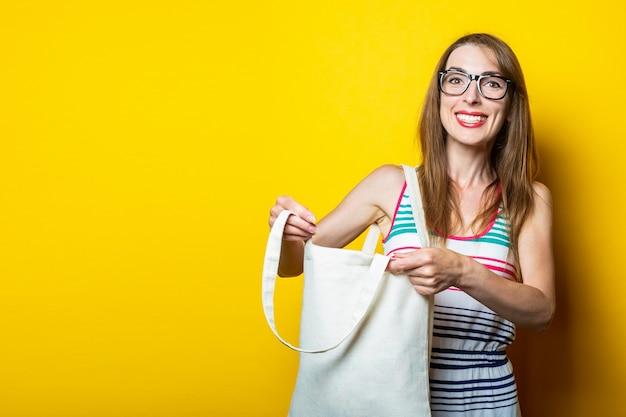 Vrolijke lachende jonge vrouw in een gestreepte jurk, in glazen met een linnen tas op een gele achtergrond.