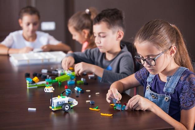 Vrolijke lachende kinderen bouwen een aannemer.