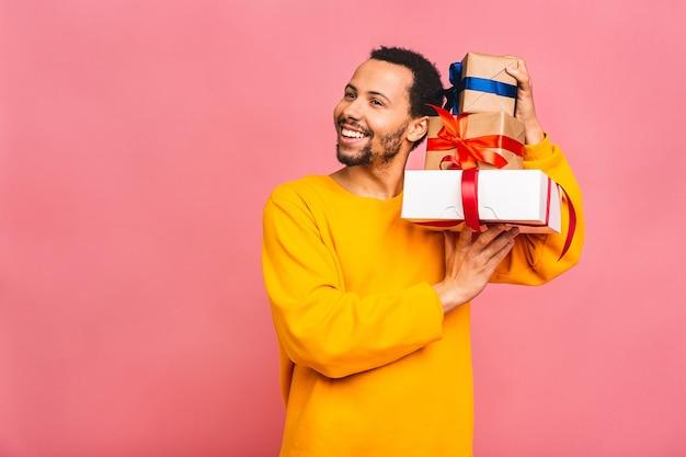 Vrolijke lachende man met verpakte huidige dozen. gelukkig jongeman feliciteren, verjaardagscadeau geven, geïsoleerd op roze.